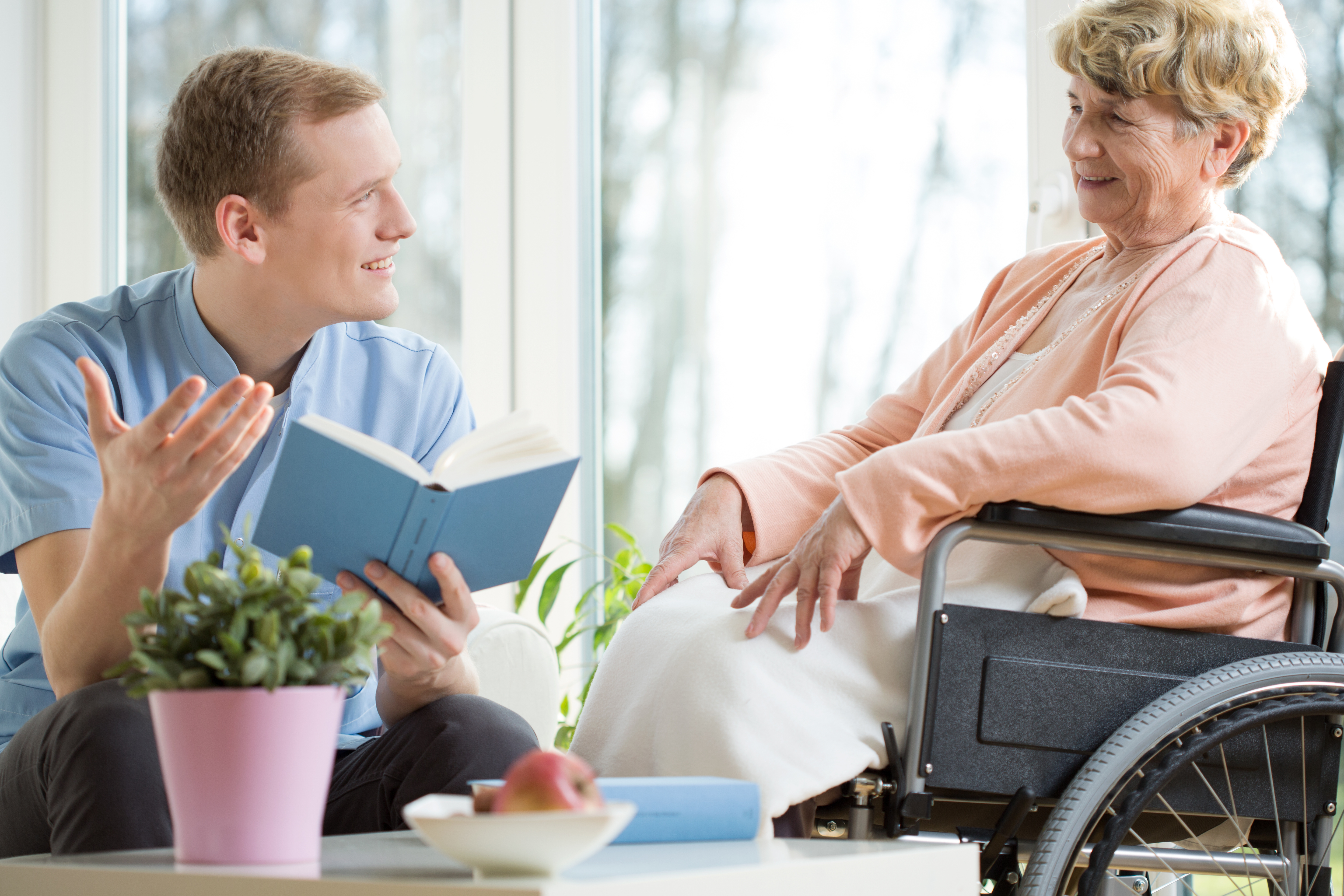 Male care assistant reading senior woman book